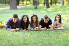 Five young friends lying on grass and using mobile phones. Two men and three women resting outdoors and browsing in smartphones, exchanging photos, chatting Royalty Free Stock Photography