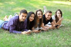 Five young friends lying on grass and using mobile phones. Two men and three women resting outdoors and browsing in smartphones, exchanging photos, chatting Royalty Free Stock Photos