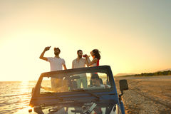Five young people having fun in convertible car at the beach at sunset. Stock Photography