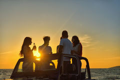 Five young people having fun in convertible car at the beach at sunset. Stock Photos