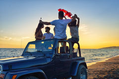 Five young people having fun in convertible car at the beach at sunset. Royalty Free Stock Photos