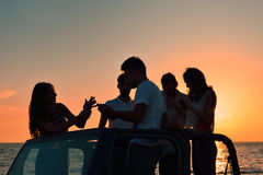Five young people having fun in convertible car at the beach at sunset. Stock Images