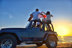 Five young people having fun in convertible car at the beach at sunset. Royalty Free Stock Photo