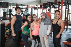 Five young people posing in fitness center. Showing muscles Stock Photography