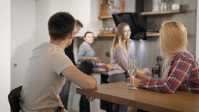 Five young people are resting on small home party in vacations, pair is drinking wine and they friends are cooking. On kitchen, roommates stock video footage