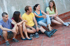 Five young people talking. Five young people sitting on a ledge, relaxing and talking to each other, smiling, having fun spending time together Stock Photo
