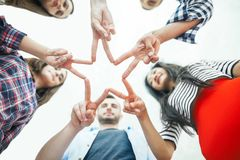 Five young smiling people make star shape from fingers. Five young smiling women and men make star shape from fingers. Happy friends or students show a sign with Stock Photo