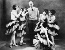 Five young women dancing around a man Stock Photos