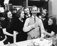 Five young women gathering around a salesman in a store Stock Photos