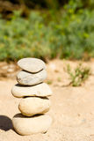 Five Zen stones stacked and balanced. A stack of five Zen stones on a beach with a blurred background Royalty Free Stock Images