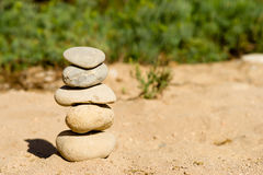 Five Zen stones stacked and balanced. A stack of five Zen stones on a beach with a blurred background Stock Photo