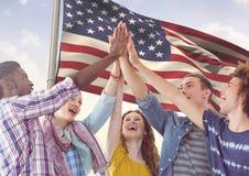Fiving élevé d'amis ensemble contre le drapeau américain Photos stock