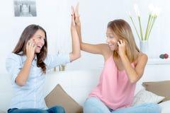 Fiving élevé de deux femmes heureuses sur le sofa à la maison Photo stock