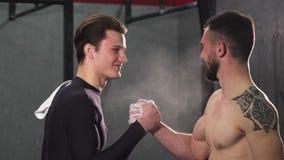 Fiving alto de dois atletas masculinos alegres no gym imagem de stock royalty free