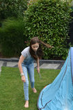 Fixing the tent. Girl fixing the tent on the ground, putting tent pegs in Royalty Free Stock Photography