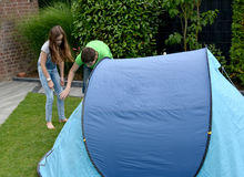 Fixing the tent. Siblings fixing the tent on the ground, putting tent pegs in Royalty Free Stock Image