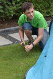 Fixing the tent. Teenage boy puts  in tent pegs. Fixing the tent on the ground Royalty Free Stock Image