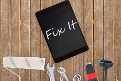 Fix it against tools and tablet on wooden background Stock Photos