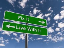Fix It Or Live With It Signs. Surrounded by a blue sky with fluffy clouds stock photos