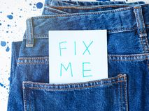 Fix me. Written message in jeans pocket. Request of help concept stock photography