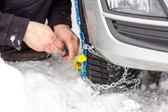 Fix snow chains on car. In winter Stock Photography