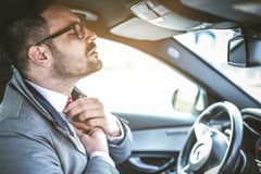 Fix the tie. Young business man sitting in car and fix the tie stock image