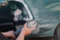 Fixande för mekanikerarbetarrepairman, genom att sandpappra den polerande bilkroppen och att förbereda sig för att måla på statio Fotografering för Bildbyråer