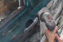 Fixande för mekanikerarbetarrepairman, genom att sandpappra den polerande bilkroppen och att förbereda sig för att måla på statio Royaltyfri Fotografi