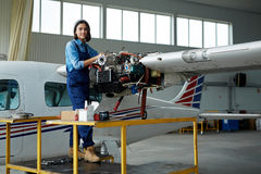 Fixandeflygplan för ung kvinna i hangar royaltyfri fotografi