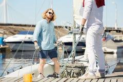 Fixanderepet för den unga mannen seglar på fartyget royaltyfria bilder