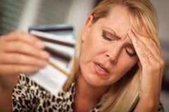 Fixation bouleversée de femme ses beaucoup de cartes de crédit Photo stock