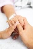 Fixation de descendant sa main de mère dans l'hôpital Photo stock