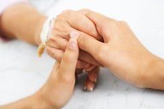 Fixation de descendant sa main de mère dans l'hôpital Images stock
