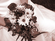 Fixation de mariée son bouquet de mariage contre sa robe Photos stock
