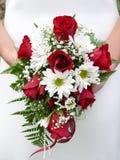 Fixation de mariée son bouquet de mariage contre sa robe Photo stock