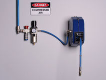 Fixed color coded compressed air line with pressure regulator and flexibly hose reel Stock Photo