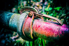 Old colorful metal pipes with clutch on a dark background with blurred grass. Coupling of red and blue pipeline close-up. Idea of cohesiveness and fixed stock photo