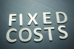 Fixed costs written with wooden letters on a green background. To understand a concept of economics and finance royalty free stock image
