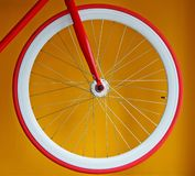 Fixed gear bicycle wheel with thin red tire and white wide rim. Yellow background royalty free stock photography