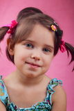 She fixed her own hair. A closeup of a dark haired, blue eyes little baby girl who fixed her own hair with pink background. Shallow depth of field royalty free stock image