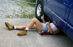 Fixed the truck!. Young woman in cutoff shorts, working on truck stock image
