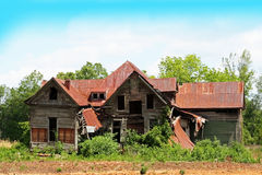 Fixer upper. Old house in field with tin roof Royalty Free Stock Photos
