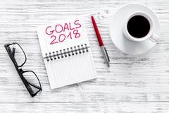 Fixez un but pendant la nouvelle année 2018 Carnet près de stylo, de verres et de tasse de café sur la vue supérieure de fond en  Photographie stock libre de droits