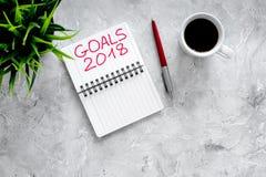 Fixez un but pendant la nouvelle année 2018 Carnet près de stylo et tasse de café sur le copyspace en pierre gris de vue supérieu Photographie stock
