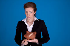 Fixing the banking crises. Young attractive businesswoman holding a piggybank with plasters on it as a money recovery concept Stock Photo