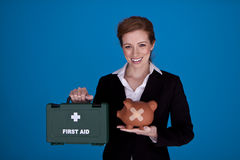 Fixing the banking crises. Young attractive businesswoman holding a piggybank and first aid kit as a money recovery concept Royalty Free Stock Images