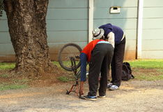 Fixing a bicycle curbside. Unemployed youths fix their bicycle curbside in post-apartheid South Africa Royalty Free Stock Photos