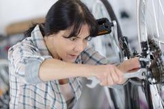 Fixing bike brake with key kit. Woman royalty free stock image