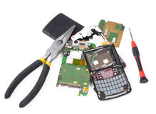 Fixing broken cell phone. Broken cell phone in pieces with tools royalty free stock photography