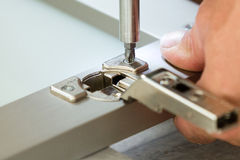 fixing cabinet door hinge Stock Photos